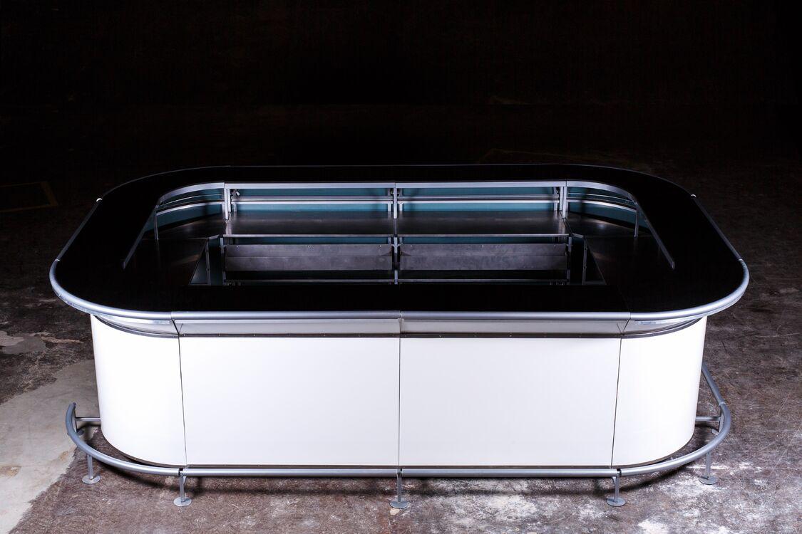 Взять в прокат Мебель Стойки  Барная стойка EXTRA; Москва , Шоссейный проезд, 12 ул.; Описание: В профессиональной барной стойке ExtraBar продумано все для организации мероприятия любого масштаба и стиля. Легкая система крепления позволит собрать бар любой формы и размера, а также подключить все барное оборудование в течение нескольких минут. Благодаря сменным панелям, LED подсветке и возможности брендинга, вы сможете стилизовать стойку под любую тематику вашего мероприятия.